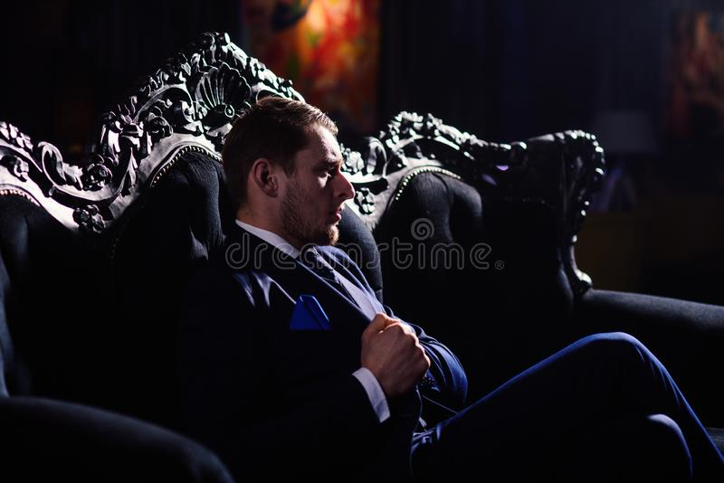 Boss in fashionable suit looks confident. Rich lifestyle, professional success, stylish furniture, money, elegance stock photos