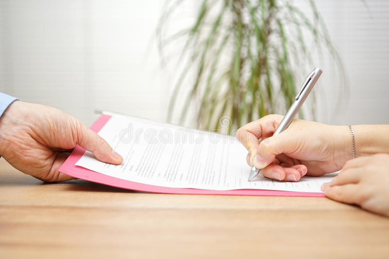 Boss gives employee dismissal contract to sign.  stock images