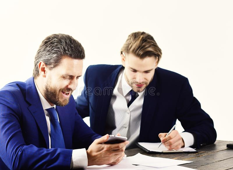 Boss gives instructions to employee. Busy people with smiling faces write papers. Boss in formal suit surfs internet. Leadership, success concept. Business stock photography