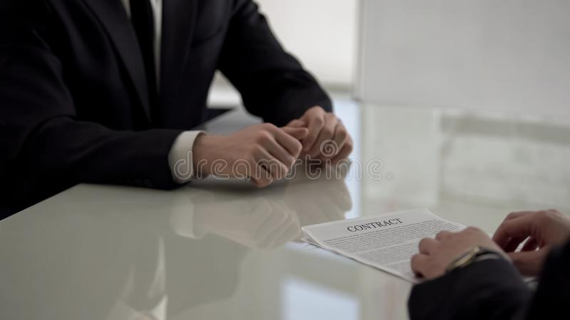 Boss giving employment contract to young job applicant, promotion assignment. Stock photo stock image