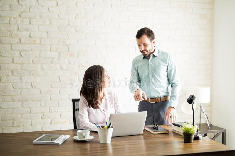 Boss giving feedback to his new employee. Attractive men giving some feedback about work to a female coworker in an office royalty free stock photo