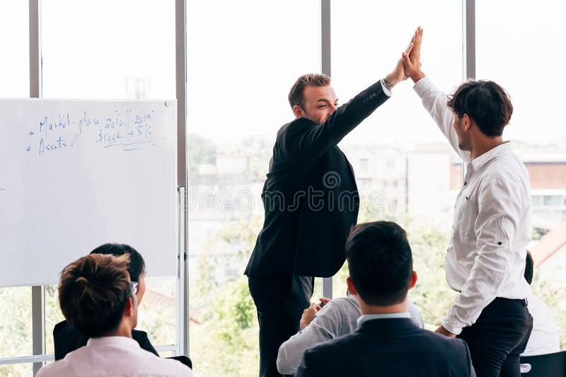 Boss giving high five to employee during conference stock image