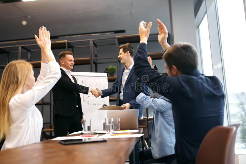 Boss handshaking, congratulating colleague with promotion stock image