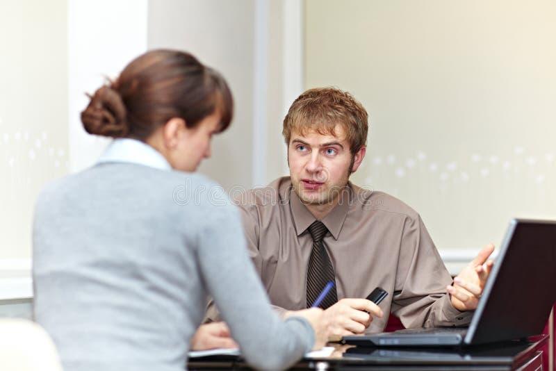 boss hans sekreterare som talar till royaltyfri bild