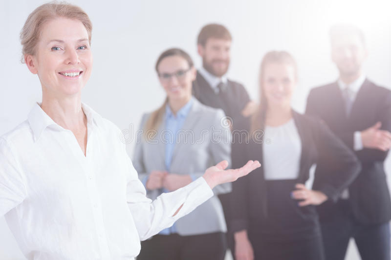 Boss and her employees. Smiling boss presenting group of her young employees royalty free stock image
