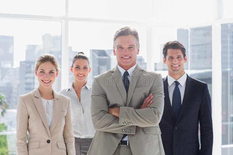 Boss with his arms folded standing with smiling colleagues behind stock photos
