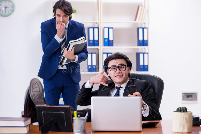 Boss and his male assistant working in the office. The boss and his male assistant working in the office stock image