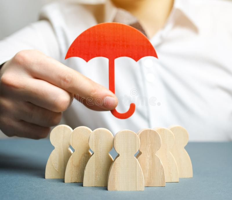 Boss holding a red umbrella and defending his team with a gesture of protection. Security and safety in a business team. Life. Insurance. Customer care, care stock photography