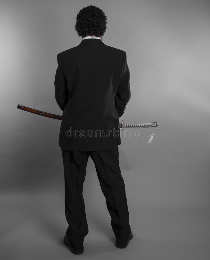 Boss, hombre de negocios agresivo con las espadas japonesas en la defensiva a imagen de archivo