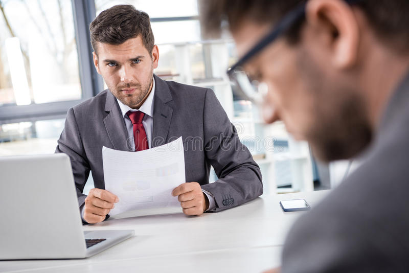 Boss looking at upset colleague at business meeting royalty free stock photos