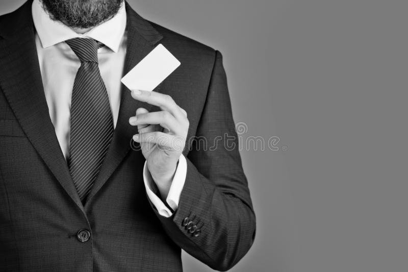 Boss or man with business or credit card, business ethics. Boss or man with business or credit card in blue formal outfit on grey background, copy space royalty free stock photo