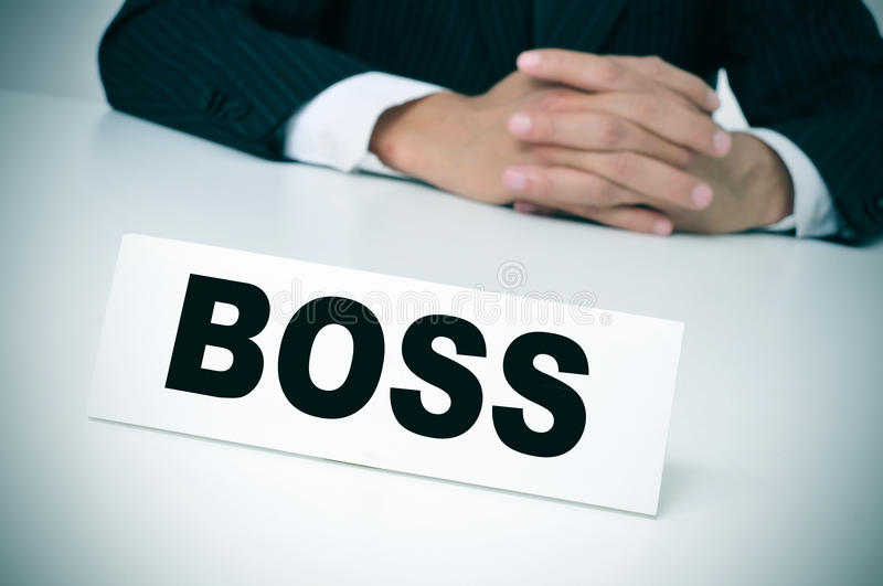 Boss. A man wearing a suit sitting in a desk with a nameplate in front of him with the word boss written in it stock photos