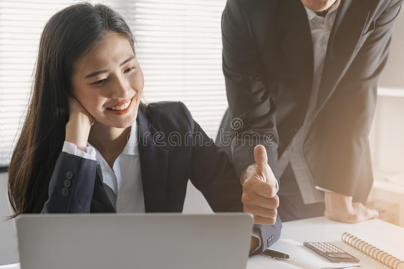 Boss/ manager male employer admires young Asian lady secretary   by thumb up for her success and good. Asia Business woman  sittin royalty free stock photography