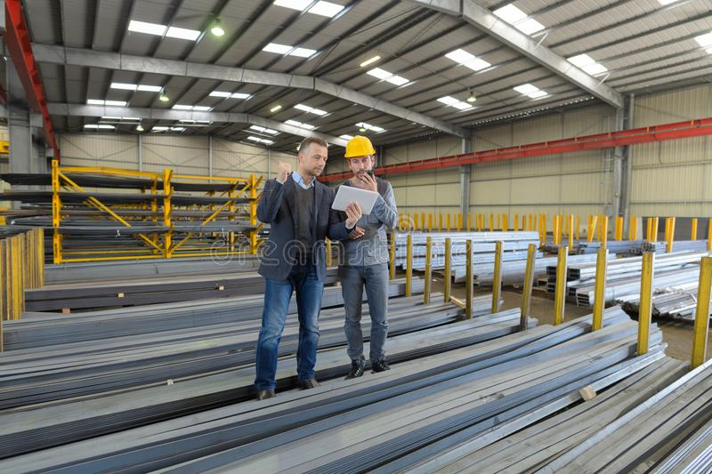 Boss and manual worker in warehouse stock images