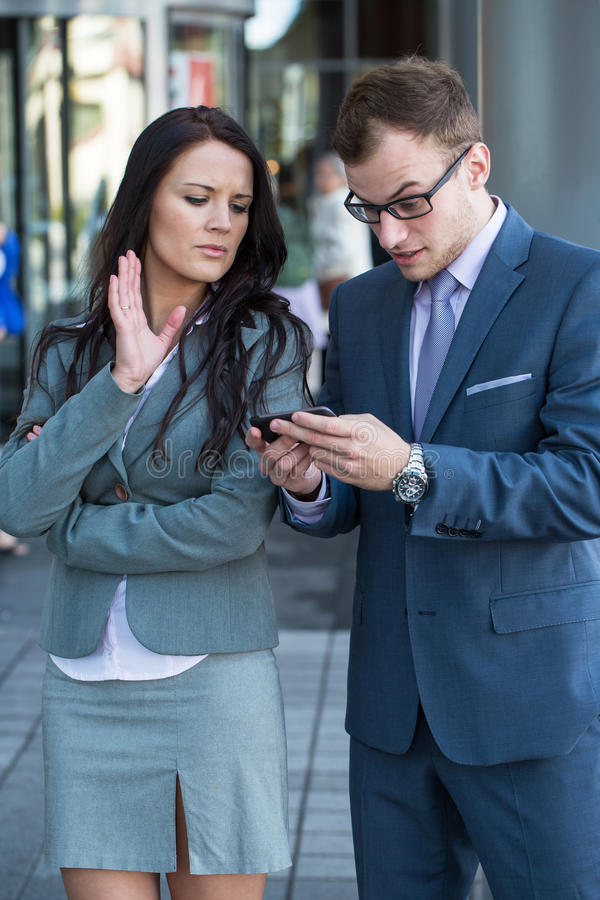 Boss with mobile phone and his secretary. The are disappointed. stock photo