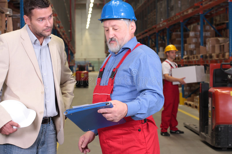 boss + old worker in warehouse stock photography