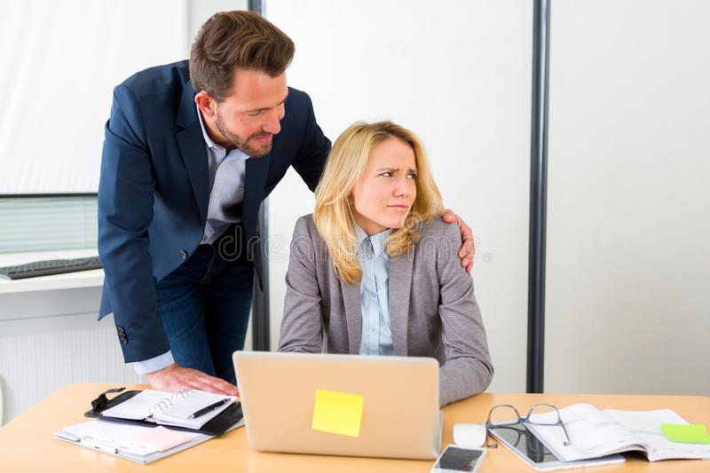 Boss putting hand on assistant shoulder - harrasment stock photo