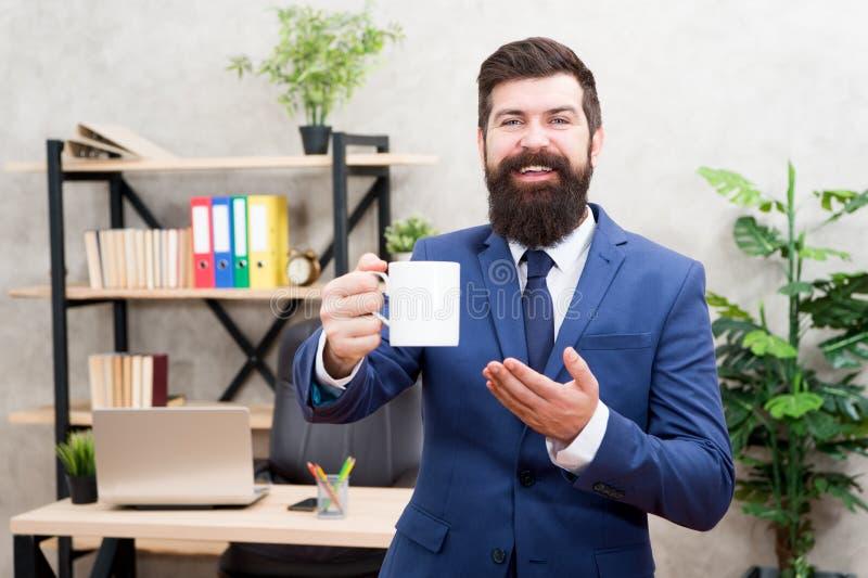 Boss que disfruta de la bebida de la energ?a Cafe?na enviciado Día del comienzo con café Soporte barbudo de la taza de café del c foto de archivo