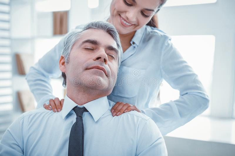 Satisfied employee having pleasant massage at work royalty free stock photo