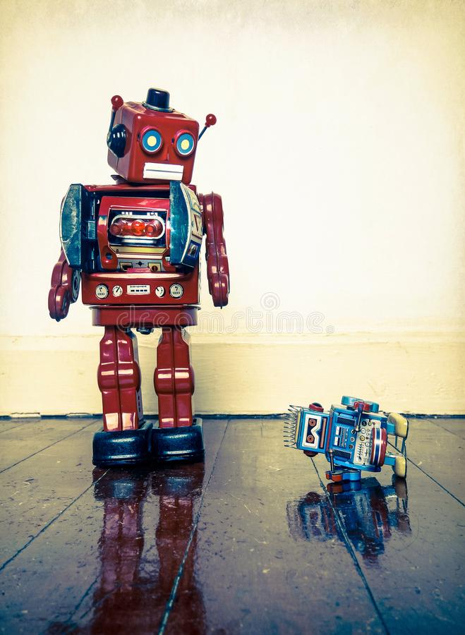 Boss robot told off. Big retro robot toy humiliates little robot on a wooden floor with reflection stock photos