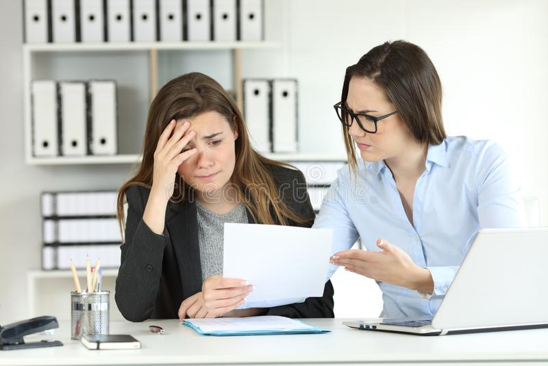 Boss scolding an intern at office stock photo