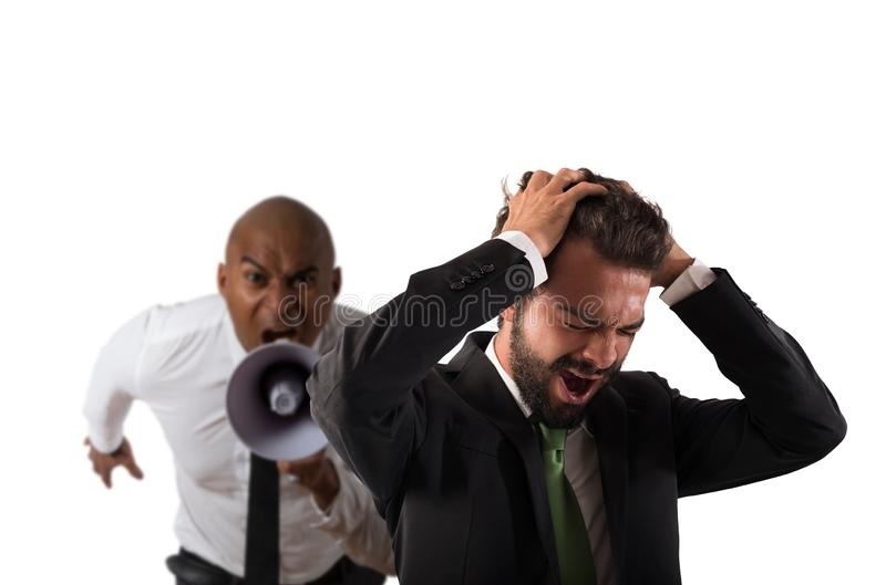 Boss scolds with megaphone a desperate employee with a verbal aggression. Concept of verbal aggression by a colleague or a boss royalty free stock photography
