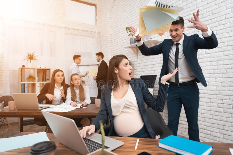 Boss se descontenta con el trabajo de la mujer embarazada joven Embarazo en el trabajo fotografía de archivo