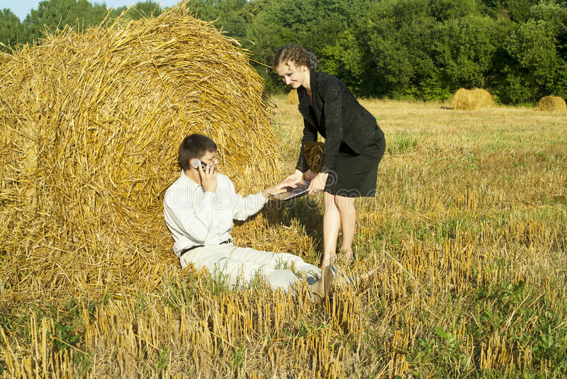 Boss and secretary in the nature. Near the haystacks royalty free stock images