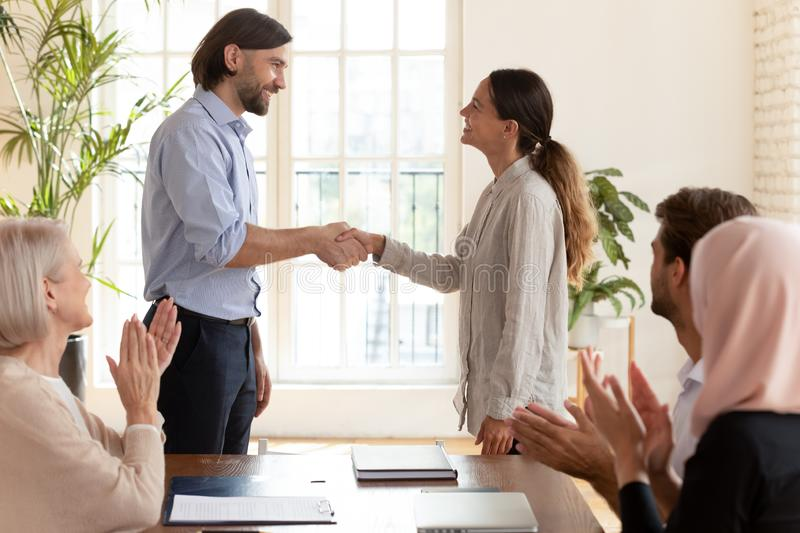 Boss shaking hand of female employee intern congratulating with promotion. Company executive boss shaking hand of proud female employee intern congratulating royalty free stock image