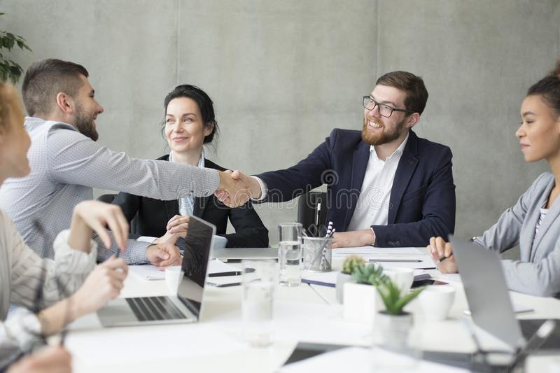 Boss shaking hands with employee at meeting. Male boss shaking hands with employee at meeting, congratulatng with new job royalty free stock photography