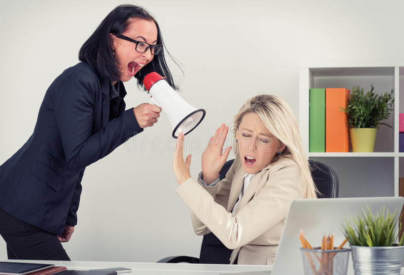Boss shouting at employee on megaphone stock photo
