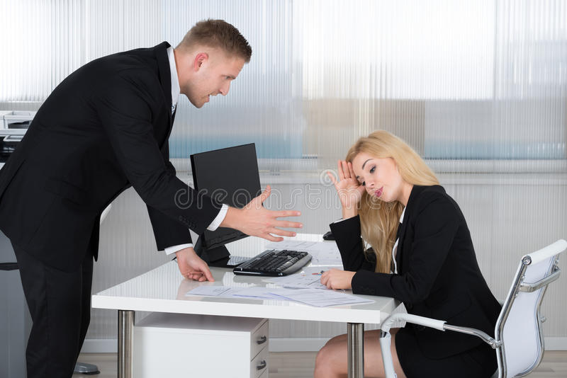 Boss Shouting At Employee Sitting At Desk. Boss shouting at female employee sitting at desk in office royalty free stock photo