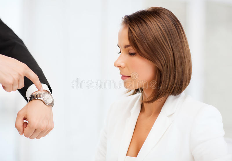 Boss showing time to stressed businesswoman royalty free stock image