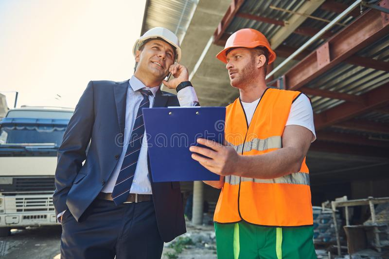 Boss is standing with foreman on construction site stock images