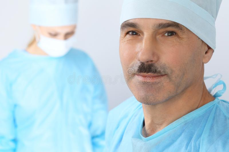 Boss surgeon is examining the operation while medical team are busy of patient. Medicine, healthcare and emergency in stock photo