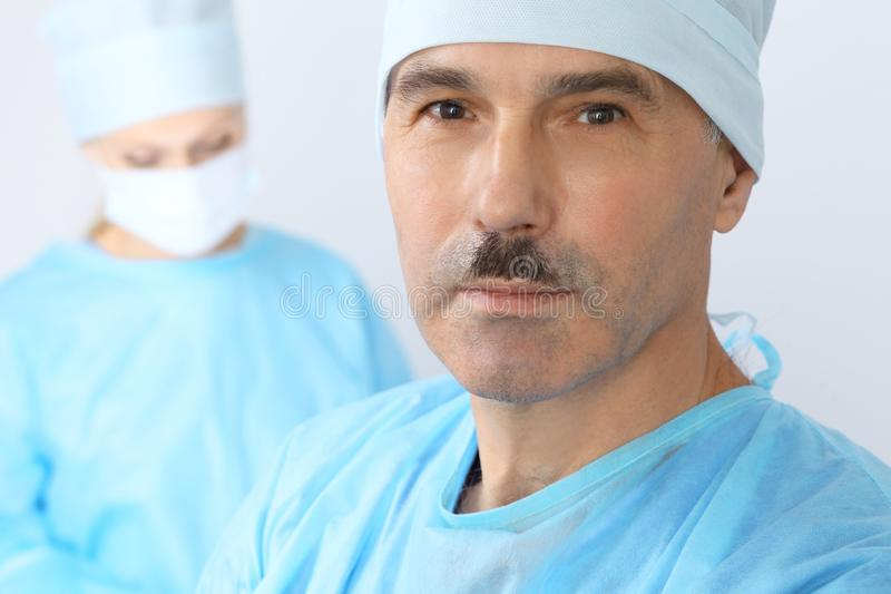 Boss surgeon is examining the operation while medical team are busy of patient. Medicine, healthcare and emergency in royalty free stock images