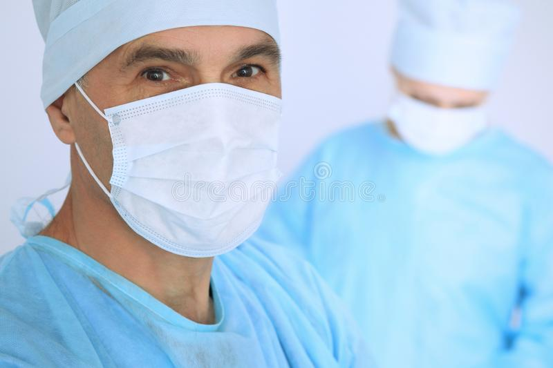 Boss surgeon is examining the operation while medical team are busy of patient. Medicine, healthcare and emergency in royalty free stock image