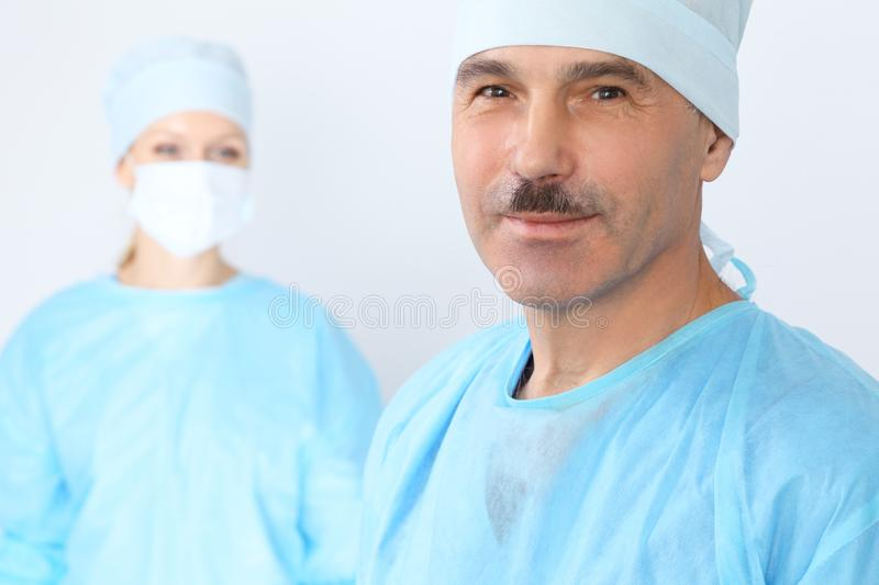 Boss surgeon is examining the operation while medical team are busy of patient. Medicine, healthcare and emergency in stock images