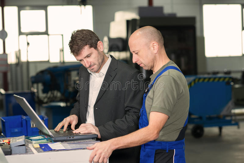 Boss and worker on work bench royalty free stock photography
