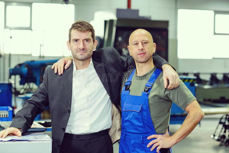 Boss and worker on work bench- hugging stock photos