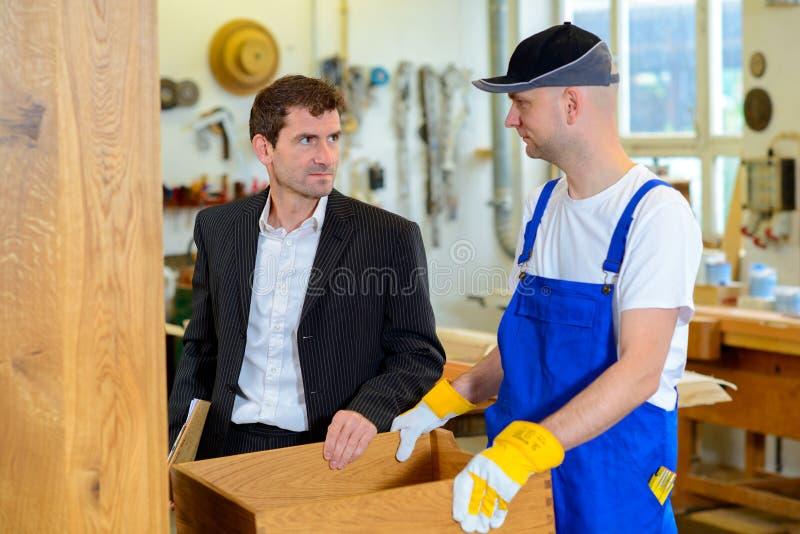 Boss y trabajador en el taller de un carpintero fotos de archivo