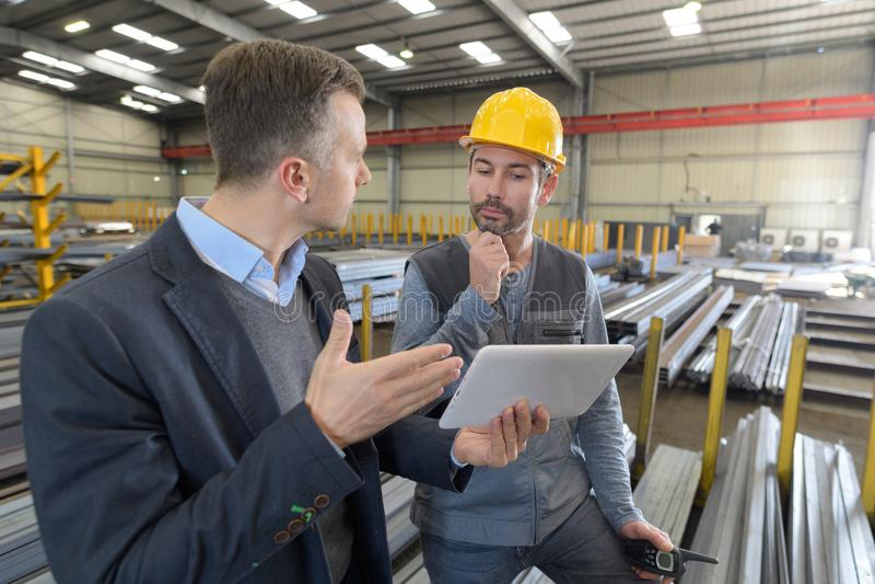 Boss y trabajador en la conversación en fábrica imagen de archivo