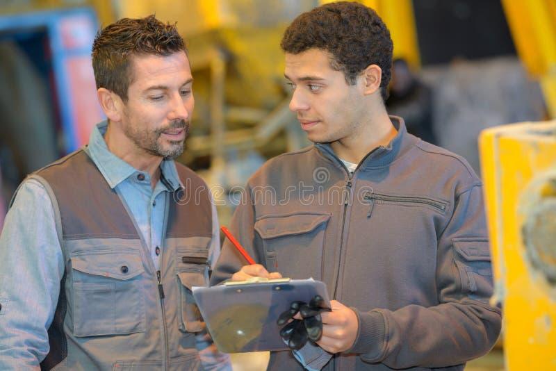 Boss y trabajador junto en taller de los carpinteros imagen de archivo libre de regalías