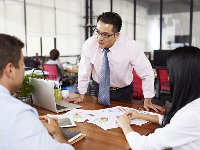 Boss yelling at subordinates. Bad-tempered asian businessman yelling at two subordinates in office royalty free stock photo