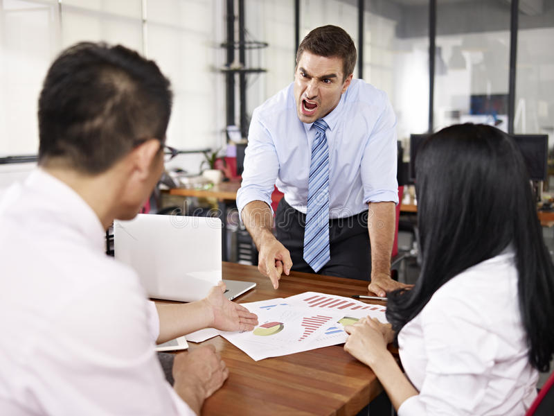 Boss yelling at subordinates. Bad-tempered caucasion business executive yelling at two asian subordinates in office royalty free stock image
