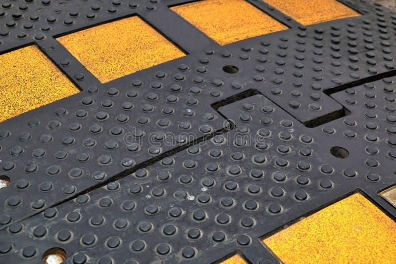 Bosse de vitesse noire avec les réflecteurs jaunes image stock