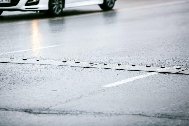 Bosse de vitesse sur la route goudronnée humide photo stock