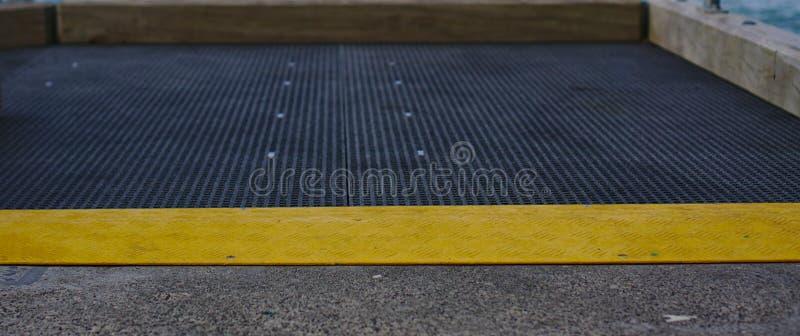 Bosse jaune de vitesse sur la terre grise image libre de droits