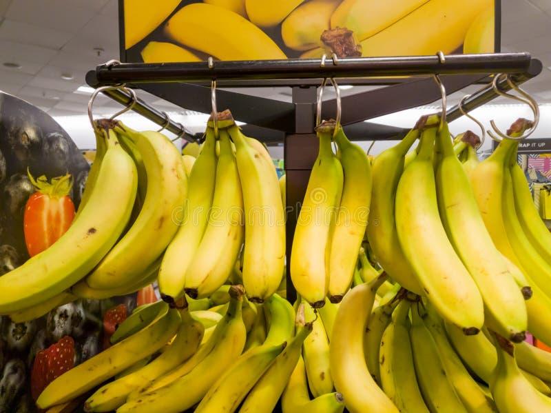 Bossen van gele Banannas voor verkoop binnen een winkel royalty-vrije stock afbeeldingen