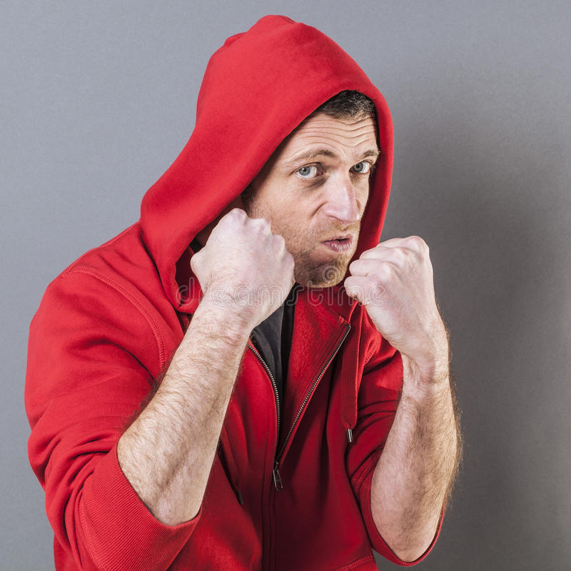 Bossy male rapper showing his fists for bullying attitude. Male fighting concept - bossy middle age male rapper showing his fists for sign of violence or royalty free stock images
